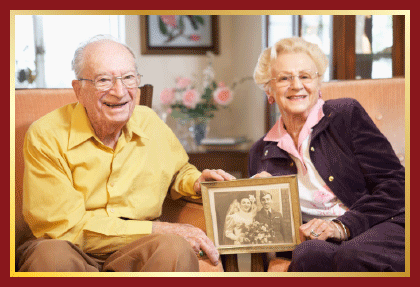 An elderly couple showing their wedding picture.